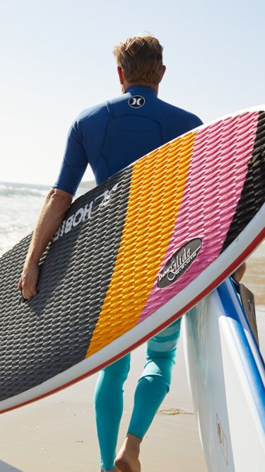 A Man Carrying A Surf Board On A Beach